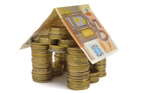 home prices: money house built with coins isolated over white background Stock Photo