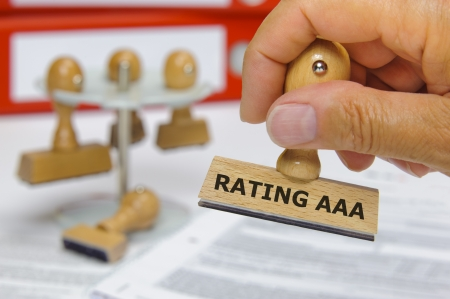 bank rate: rubber stamp in hand marked with rating aaa