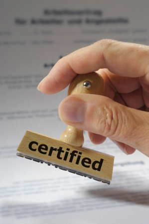 rubber stamp in hand marked with certified Stock Photo