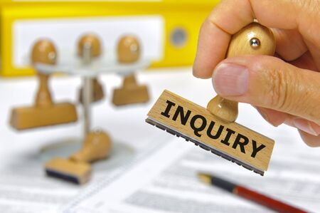 inquiry: rubber stamp in hand marked with inquiry