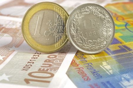 swiss franc: euro and swiss franc coin on banknotes