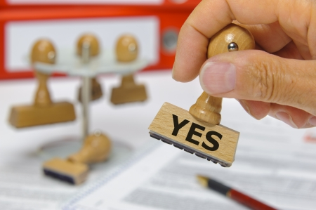 rubber stamp in hand marked with yes Stock Photo - 15542254