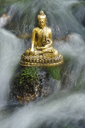 buddhism prayer belief: buddha figure is sitting in water cascade Stock Photo