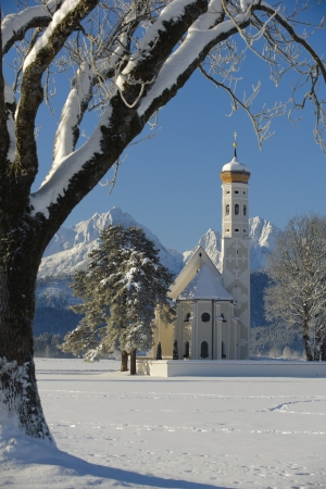 famous church St. Coloman in bavaria, germany with alps mountains at sunny winter day photo
