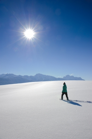 single woman with snow shoes on a walk in fresh snow powder in bavaria, germany photo