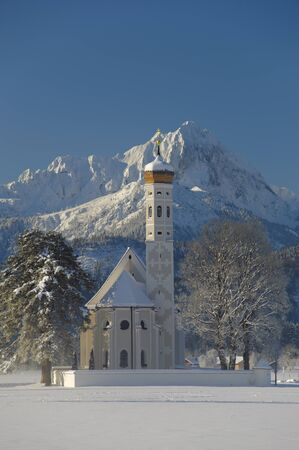 schwangau: famous church St  Coloman in upper bavaria, germany, at winter with snow and alps mountain in background