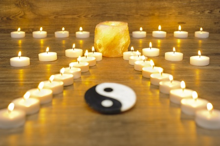japanese zen garden with candles and stone of yin and yang photo