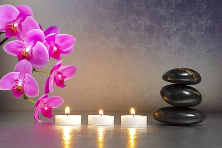 spa still life: ZEN with candle, stacked stones and orchid flower Stock Photo