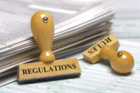 compliance: rubber stamps marked with regulations and rules