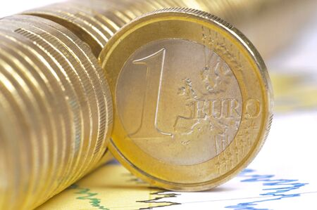 paper currency: one single euro coin on business chart Stock Photo