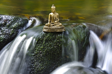 buddha tranquil: Buddha figure is sitting in water cascade Stock Photo