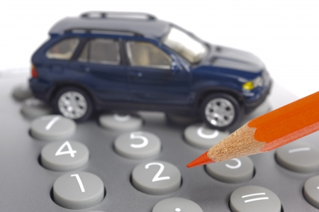 model car on financial calculator with red pencil photo