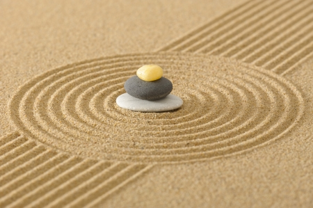 ZEN garden in sand with stacked stones photo