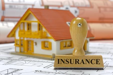 protection plan: insurance marked on rubber stamp with model house and construction plan