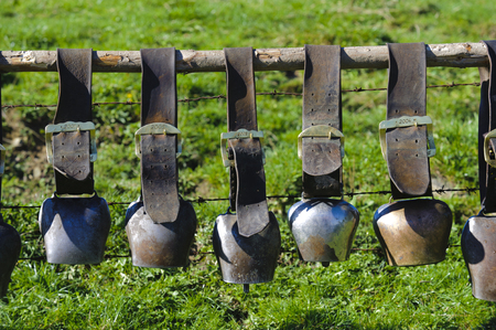 group of cow bells in line on fence in Bavaria photo
