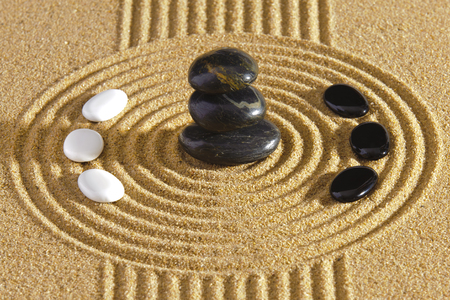 Japanese ZEN garden with stacked stones of yin and yang  in raked sand photo