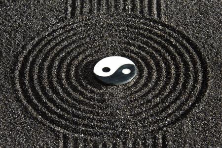 yin y yang: Jardín zen japonés con piedra del yin y el yang en la arena rastrillada Foto de archivo