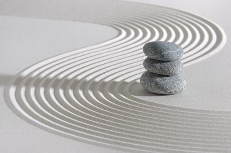 Jardin zen japonais avec des pierres empilées dans le sable ratissé