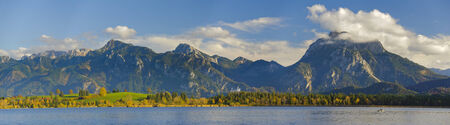 panorama landscape in Bavaria with alps mountains and lake Forggensee photo