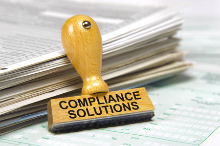 compliance solutions marked on rubber stamp Foto de archivo