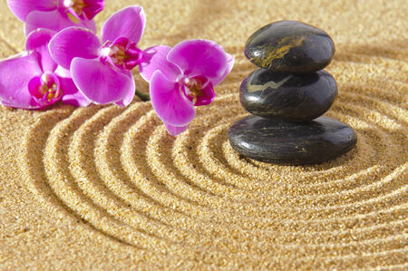 Japanese ZEN garden in sand with stacked stones and orchid flower photo