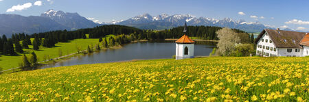 rural panorama landscape in Bavaria with lake, chapel, farmhouse and alps mountains photo