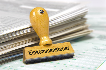 income tax marked on german rubber stamp Stock Photo - 29370521