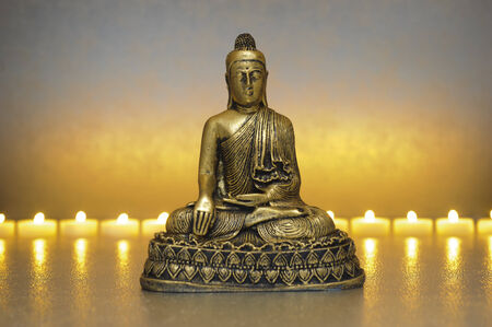 candle light: Buddha sitting in meditation with line of candle lights