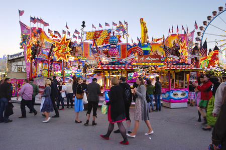 traditional events: MUNICH, GERMANY - SEPTEMBER 23, 2014: The Oktoberfest in Munich is the biggest beer festival of the world. The visitors have lot of fun with many amusement huts and shops for food, gifts and souvenirs. Editorial