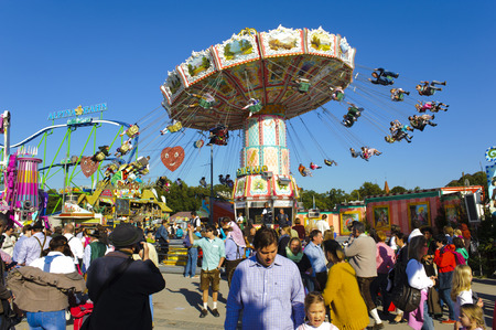 MUNICH, GERMANY - SEPTEMBER 23, 2014: The Oktoberfest in Munich is the biggest beer festival of the world. The visitors have lot of fun with many amusement huts and big carousels.