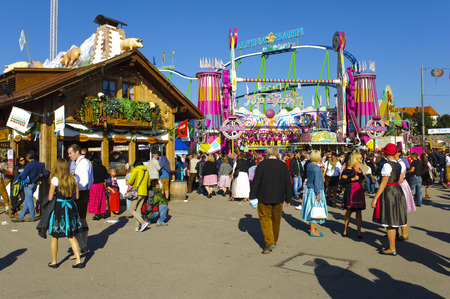 MUNICH, GERMANY - SEPTEMBER 23, 2014: The Oktoberfest in Munich is the biggest beer festival of the world. The visitors have lot of fun with many amusement huts and shops for food, gifts and souvenirs.
