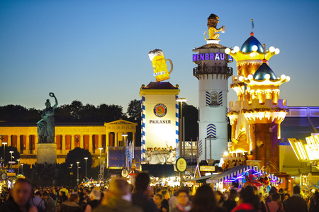 MUNICH, GERMANY - SEPTEMBER 23, 2014: The Oktoberfest in Munich is the biggest beer festival of the world.The guests are walking at the mainstreet wit the towers of bavarian beer tents beside statue of patron Bavaria