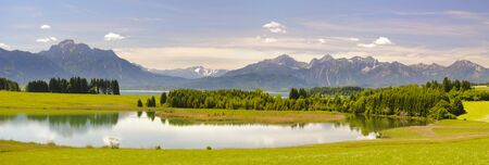 Panorama landscape in Bavaria at alps mountains and lake Forggensee photo