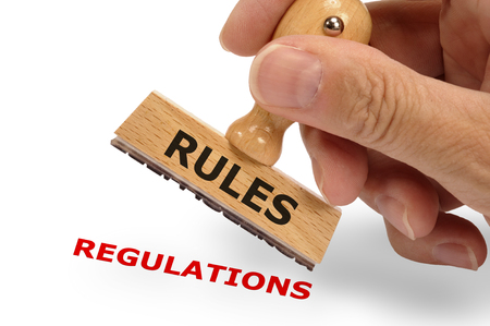 government regulations: rules and regulations marked on rubber stamp Stock Photo