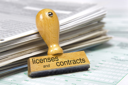 legal office: licenses and contracts printed on rubber stamp over documents Stock Photo