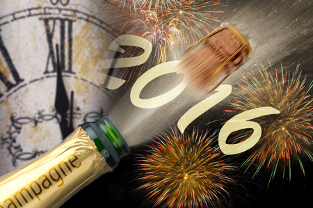 Happy new year 2016 with popping champagne and clock at midnight