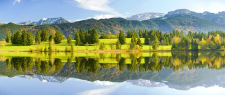 panorama landscape in Bavaria at alps mountains with mirroring in lake photo