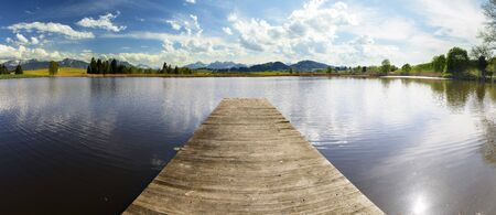 wide panorama landscape in Bavaria, Germany, with lake and wooden landing stage