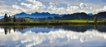 mirroring: panorama landscape in Bavaria with alps mountains mirroring in lake