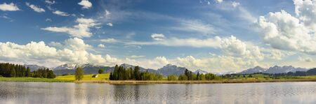 nature green: panorama landscape in Bavaria with alps mountains mirroring in lake