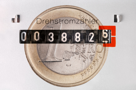 energy costs: electricity counter with Euro coin as symbol for high energy costs Stock Photo