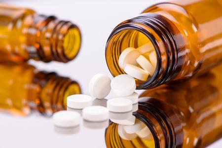 Medicina alternativa con pastillas blancas y botellas de medicina marrón Foto de archivo - 47271843