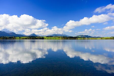 mirror on the water: panorama landscape in Bavaria with mountains mirroring in water Stock Photo