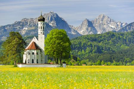 romance sky: landmark church St. Coloman in Bavaria Stock Photo