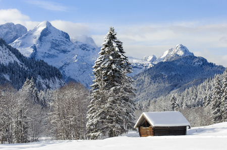 old barn in winter: beautiful landscape in Bavaria with alps mountains in snow with little wooden hut Stock Photo