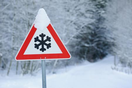 advertencia: se�al de tr�fico advierte de nieve y hielo en la carretera Foto de archivo