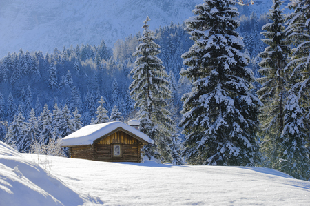 cabins: beautiful landscape in Bavaria with alps mountains in snow with little wooden hut Stock Photo