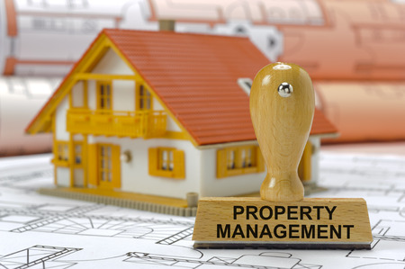 property management printed on rubber stamp with model house and plan Archivio Fotografico