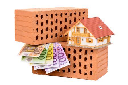 dinero euros: ladrillos para la construcción de viviendas y dinero euro con la casa modelo Foto de archivo