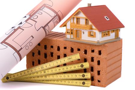 materiales de construccion: ladrillos para la construcción de viviendas y la herramienta con la casa modelo